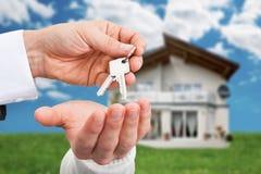 Agente immobiliare che fornisce le chiavi al proprietario contro la nuova casa Fotografie Stock