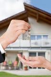 Agente immobiliare che fornisce le chiavi al proprietario contro la nuova casa Fotografia Stock