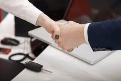 Agente immobiliare che fornisce le chiavi della casa al cliente dopo la firma di contratto immagine stock