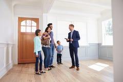 Agente immobiliare che mostra famiglia ispana intorno alla nuova casa fotografia stock libera da diritti