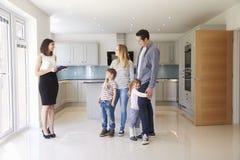 Agente immobiliare che mostra giovane famiglia intorno alla proprietà da vendere immagine stock