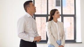 Agente immobiliare che mostra la nuova stanza dell'ufficio ai clienti stock footage