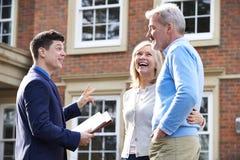 Agente immobiliare che mostra le coppie mature intorno alla Camera da vendere Immagine Stock
