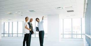 Agente immobiliare che mostra nuovo spazio ufficio ai clienti immagini stock libere da diritti