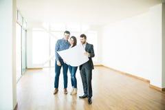Agente immobiliare che mostra piano architettonico alle coppie nella nuova casa fotografia stock