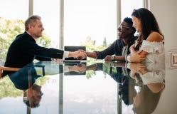 Agente immobiliare che si congratula le coppie dopo un affare della proprietà immagine stock