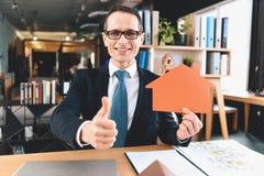Agente immobiliare che si siede allo scrittorio in ufficio L'agente immobiliare sta mostrando l'icona del ritaglio di nuova casa immagine stock