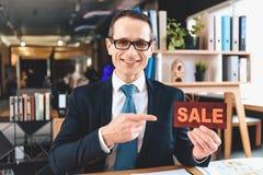 Agente immobiliare che si siede allo scrittorio in ufficio L'agente immobiliare sta presentando il segno di vendita fotografia stock libera da diritti