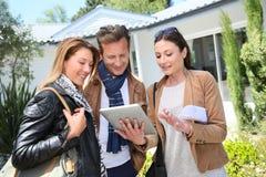 Agente immobiliare con i clienti davanti alla loro nuova casa fotografia stock libera da diritti