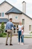 agente immobiliare con la compressa digitale che stringe mano della donna immagine stock