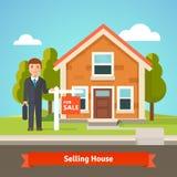 Agente immobiliare e casa con per il segno di vendita Immagine Stock Libera da Diritti