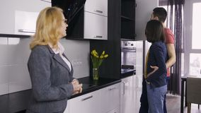 Agente immobiliare e coppie che parlano allo studio della cucina stock footage