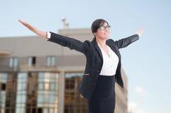 Agente immobiliare femminile allegro con le armi stese Fotografia Stock Libera da Diritti