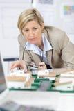 Agente immobiliare femminile che esamina il modello della proprietà di nuovo-configurazione immagini stock libere da diritti