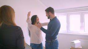 Agente immobiliare femminile che fornisce le chiavi dalla nuova casa alle giovani mani emozionanti felici di scosse e delle coppi