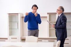 Agente immobiliare maschio e cliente maschio nell'appartamento fotografie stock