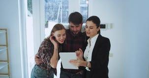 Agente immobiliare moderno della casa prendparteere alla casa con il suo cliente e dall'entrata lei che rappresenta la casa video d archivio