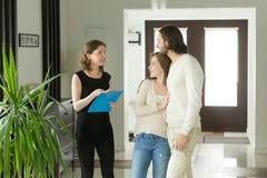 Agente immobiliare o proprietario che mostra casa di lusso moderna all'abitudine delle coppie immagini stock