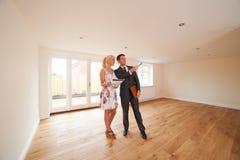 Agente immobiliare Showing Young Woman intorno alla nuova proprietà vuota immagine stock