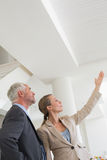 Agente immobiliare sorridente che mostra soffitto al compratore potenziale Fotografia Stock