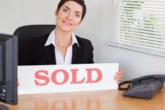 Agente immobiliare sorridente con un comitato venduto Fotografia Stock Libera da Diritti