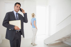Agente immobiliare sulla chiamata con la donna vaga nel fondo Immagini Stock Libere da Diritti