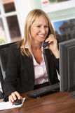 Agente imobiliário fêmea que fala no telefone na mesa Fotos de Stock Royalty Free