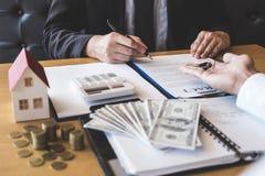 Agente imobiliário que dá chaves da casa ao cliente após ter assinado bens imobiliários do contrato do acordo com formulário de c foto de stock royalty free