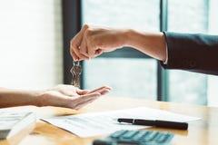 Agente imobiliário que dá chaves da casa para equipar e assinar o acordo no offi imagens de stock