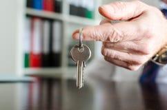 Agente imobiliário que mostra chaves da casa Fotografia de Stock Royalty Free