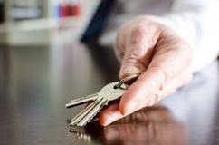 Agente imobiliário que mostra chaves da casa Fotografia de Stock