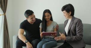 Agente inmobiliario atractivo joven de la reunión de los pares, contrato de firma con el agente de sexo femenino almacen de metraje de vídeo