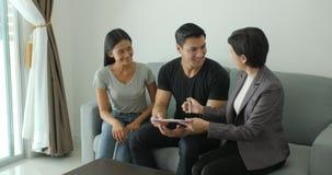 Agente inmobiliario atractivo joven de la reunión de los pares, contrato de firma con el agente de sexo femenino almacen de video