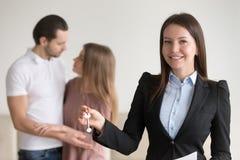 Agente inmobiliario atractivo que lleva a cabo llaves al apartamento, propiedad Imagen de archivo libre de regalías