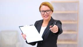 Agente inmobiliario con el acuerdo del arriendo o de compra almacen de metraje de vídeo