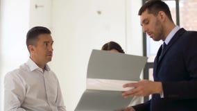 Agente inmobiliario con la carpeta que muestra documentos a los clientes almacen de metraje de vídeo