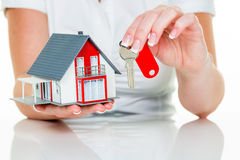 Agente inmobiliario con la casa y la llave Imágenes de archivo libres de regalías