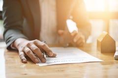 Agente inmobiliario con la mano del modelo de la casa que pone el contrato de firma Fotografía de archivo libre de regalías