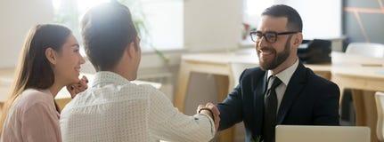 Agente inmobiliario confiado que saluda a la pareja de matrimonios joven de los clientes en oficina foto de archivo