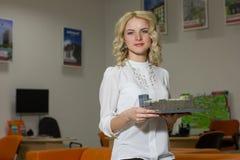 Agente inmobiliario de la muchacha que lleva a cabo un hogar modelo imagen de archivo libre de regalías
