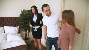 Agente inmobiliario de sexo femenino que hace frente a los pares jovenes, mostrando el dormitorio del apartamento almacen de metraje de vídeo