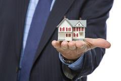 Agente inmobiliario de sexo masculino Holding Miniature House en palma Fotografía de archivo libre de regalías