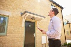 Agente inmobiliario de sexo masculino que considera para arriba un exterior de la casa Fotos de archivo