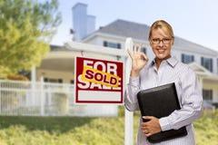 Agente inmobiliario delante de la muestra y de la casa vendidas Imagen de archivo