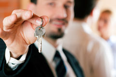 Agente inmobiliario en el apartamento que da claves a los pares Fotos de archivo