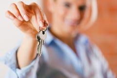 Agente inmobiliario en el apartamento vacío que da claves Imagenes de archivo