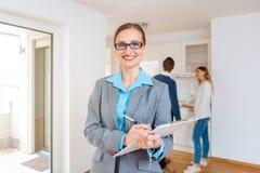 Agente inmobiliario en nueva casa con los pares que hacen el viaje en el fondo imagenes de archivo