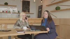 Agente inmobiliario femenino que comunica con el cliente en café metrajes
