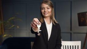 Agente inmobiliario femenino que da las llaves del apartamento a la cámara almacen de metraje de vídeo