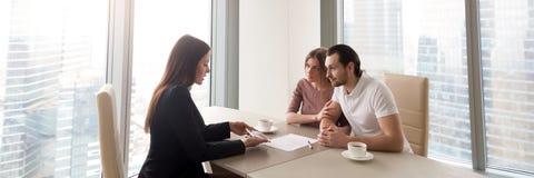 Agente inmobiliario horizontal de la imagen y pares jovenes que discuten plan de la nueva casa imágenes de archivo libres de regalías